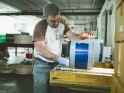 Brian sanding down a royal blue drum